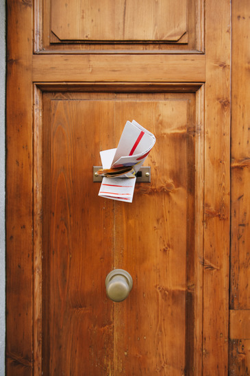 Multiple magazines in a letterbox of a wooden door. Focus is on the newspaper and magazines.